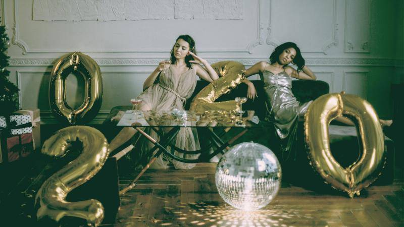 2 girls in new year party dresses sitting on a couch, disco ball on the floor, and balloons 2, 0, 2, 0 scattered.