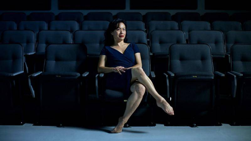 University of North Carolina professor Kim Jones sitting on the first row of grey theatre chairs, with a blue dress, legs crossed and bare feet.