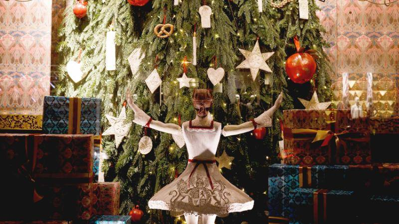 A puppet ballerina in a white tutu with red trim raising her arms towards a tall decorated christmas tree she is facing.