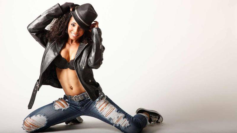 MaDonna Grimes kneeling on the floor, with ripped jeans, black bra, leather jacket, a black hat and a smile.