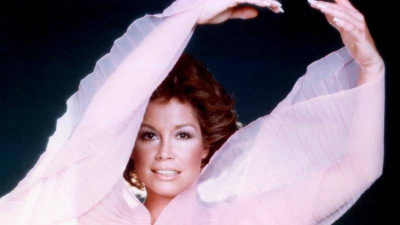 Close up of Mary Tyler Moore in a sheer pink top, arms above head.