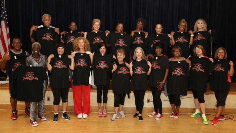 Miami Heat Golden Oldies posing as a group each holding a black t-shirt with their logo.