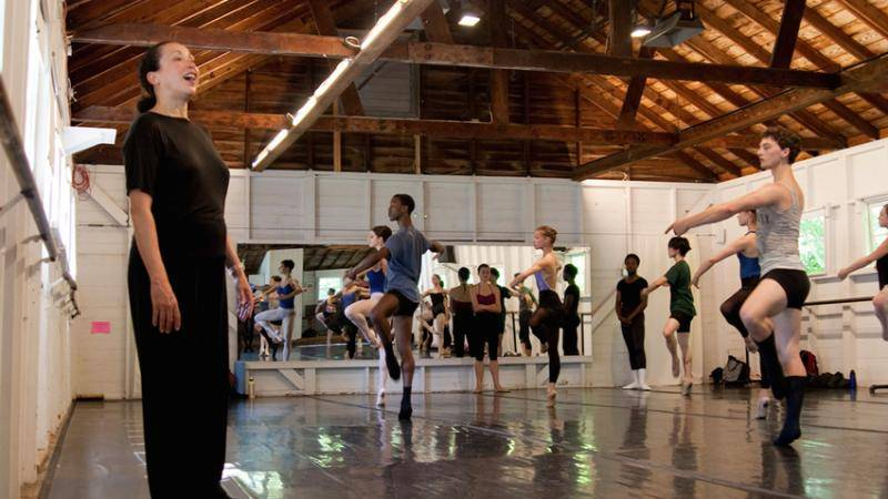 A dance teacher at Jacob's Pillow in class with young students in a relevé passé position.