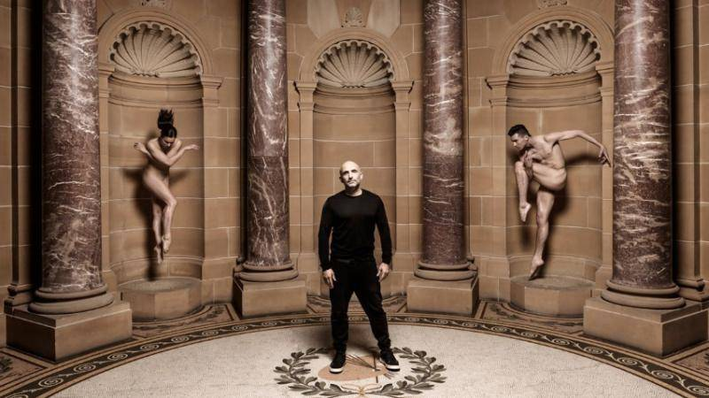 Rafael Bonachela standing in the middle of a greek alcove at the National Gallery of Australia, with 2 nude dancers on either side posing as statues.